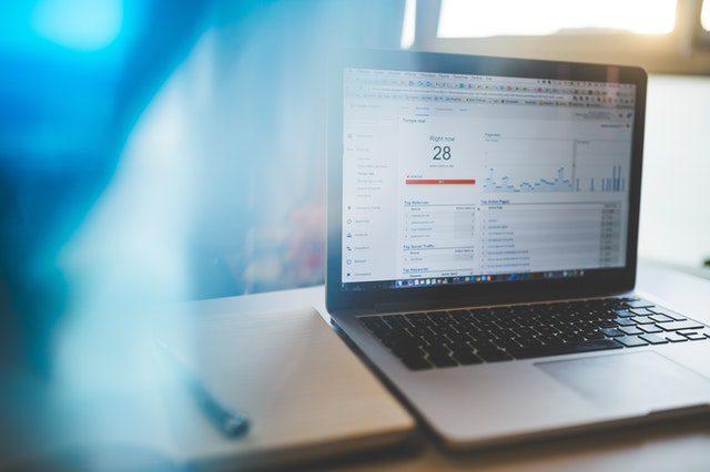 Photo d'un pc portable ouvert sur un bureau avec sur l'écran des statistiques SEO